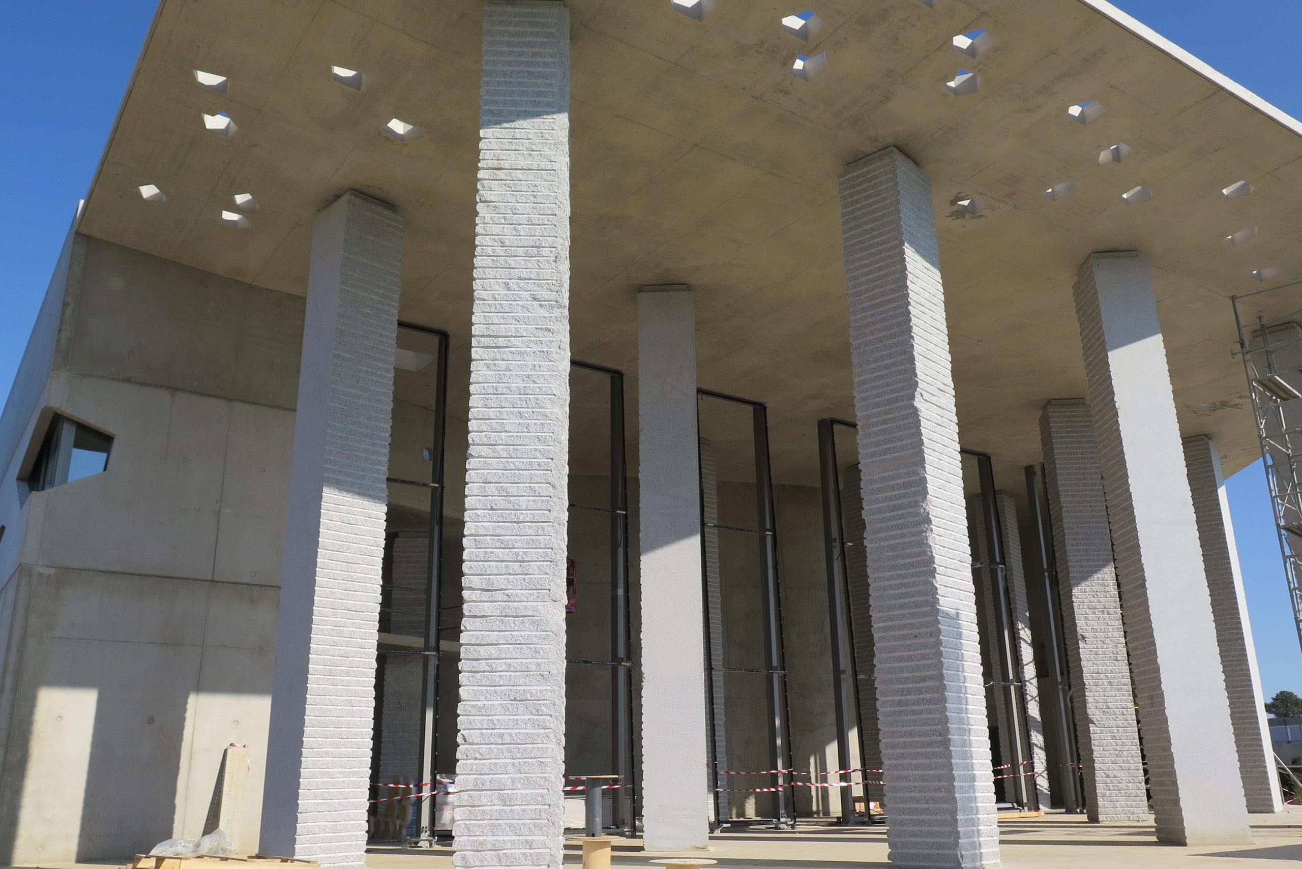 A large concrete hood with scattered cutouts held up by 13 granite support columns covers the courtyard of the future Agora auditorium.  Image: CEMEX France