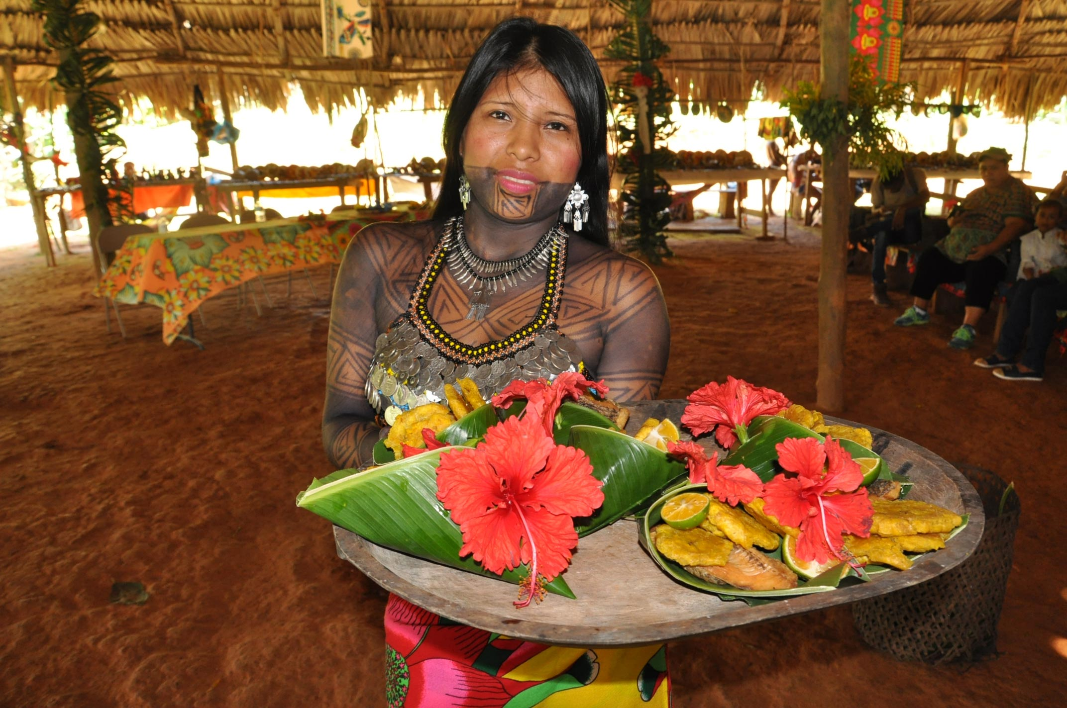 An Emberá woman in traditional garb displays a tray of food decorated with flowers